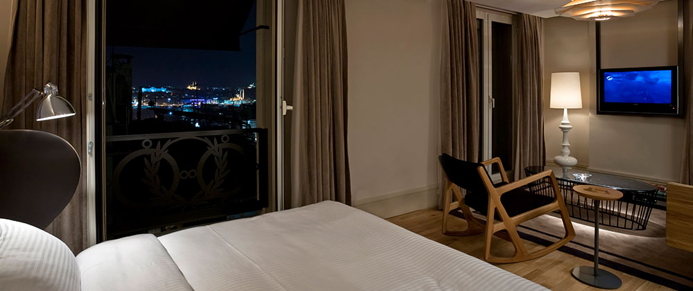 Bed, living room and view of King Panoramic room at Witt Istanbul Hotel.