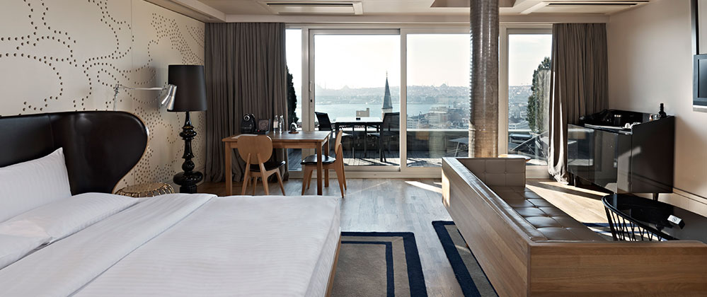 Bed, living room and view of King Panoramic with Terrace room at Witt Istanbul Hotel.