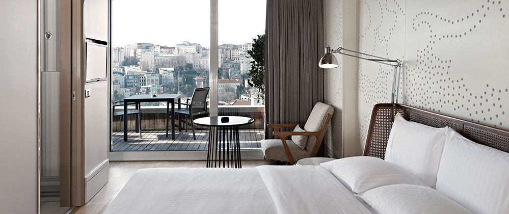 Bed and armchair in Queen Panoramic with Terrace room at Witt Istanbul Hotel.